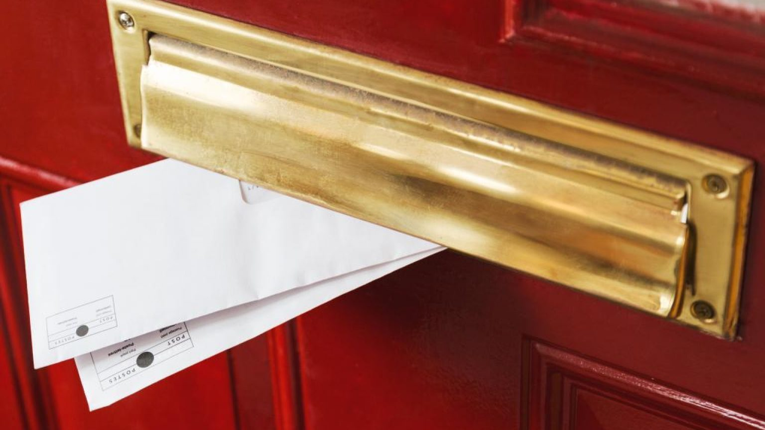 Mail peeks out from a brass letterbox 1024x683
